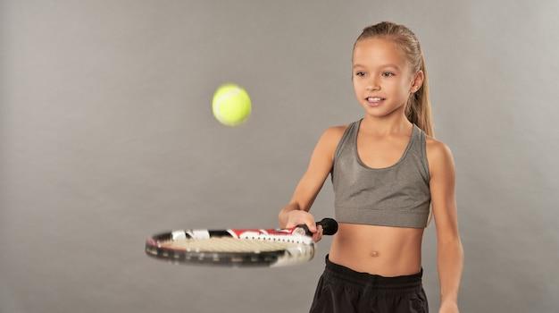 ラケットでテニスボールをバウンスする愛らしいうれしそうな女の子