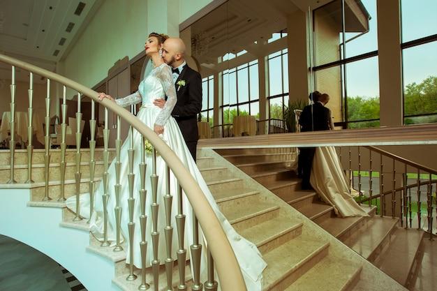 Очаровательны молодожены обнимаются и целуют друг друга на лестнице