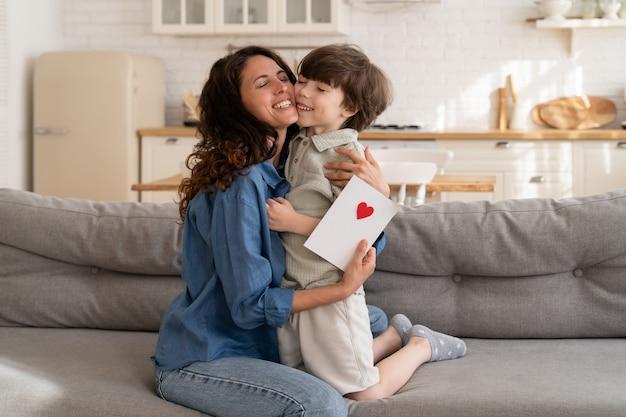 愛らしい男の子は、グリーティングカードを提示するお母さんを抱きしめる母の日または誕生日でお母さんを祝福します