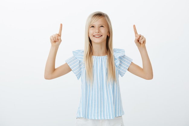 Adorable kid discussing cloud shapes with friend. portrait of creative happy young girl with blond hair, smiling broadly from positive emotions, looking and pointing up with raised index fingers