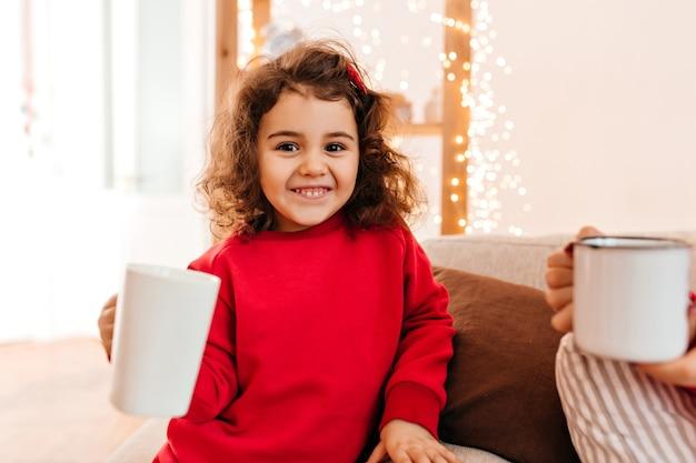 차를 마시는 사랑스러운 아이. 빨간색 파자마에 매력적인 초반 여자의 실내 촬영.