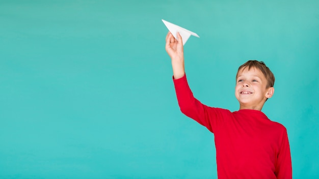 Adorable kid holding a paper airplane with copy space