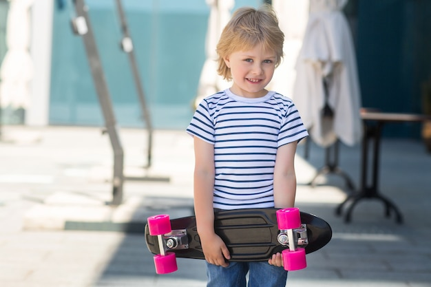 Adorable kid outdoors. cute pretty child smiling at camera. casual boy on summer time skating on a skateboard. holding skateboard like a present