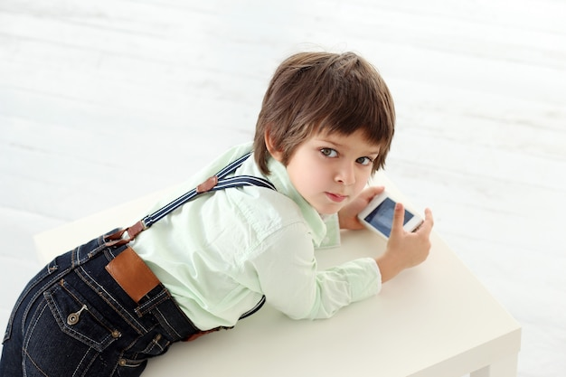 Adorable kid playing with a smartphone