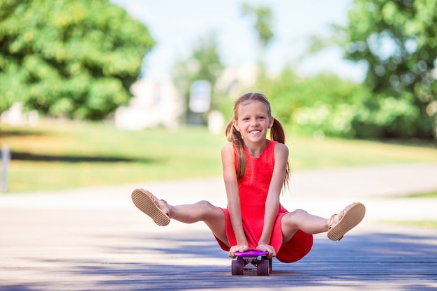 Adorable kid riding skateboard in summer park.