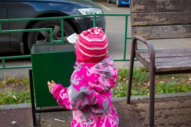 Очаровательный ребенок выбрасывает мусор в мусорное ведро на улице