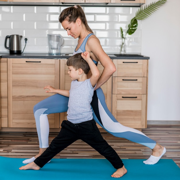 Adorable kid training together with mom