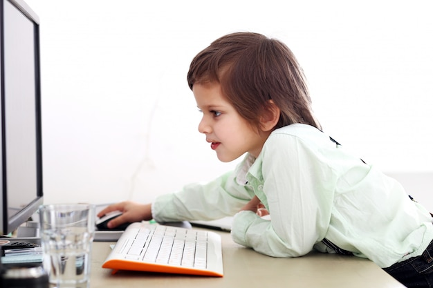 Adorable kid using a computer