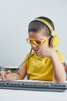 An adorable kid in a yellow t-shirt with a headphone listening online course.