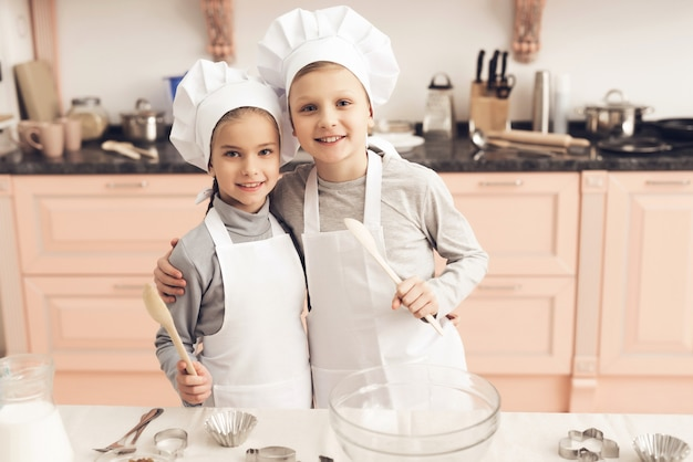 Adorable kids boy and girl have fun at kitchen.