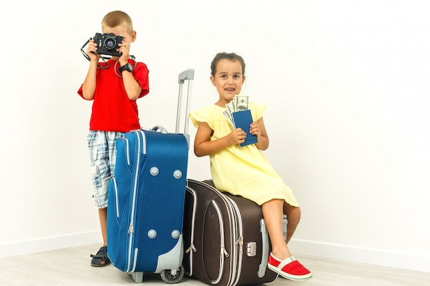 Adorable kids brother and sister with a suitcase sitting while travelling