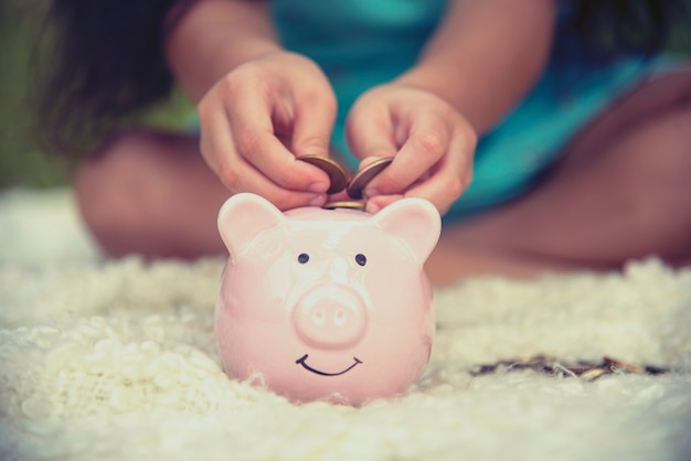 Adorable kids hands saving coins in piggy bank. happy little investment saving money for happiness future.
