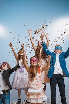 愛らしい子供たちが一緒に誕生日パーティーでカラフルな紙吹雪を投げるのを楽しんでいます。彼らはさまざまなゲームで一緒に遊んで、装飾されたスタジオで時間を過ごします。子供とイベントのコンセプト