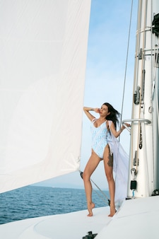 An adorable lady standing and posing on sailboat or yacht in the sea wearing modern white swimsuit
