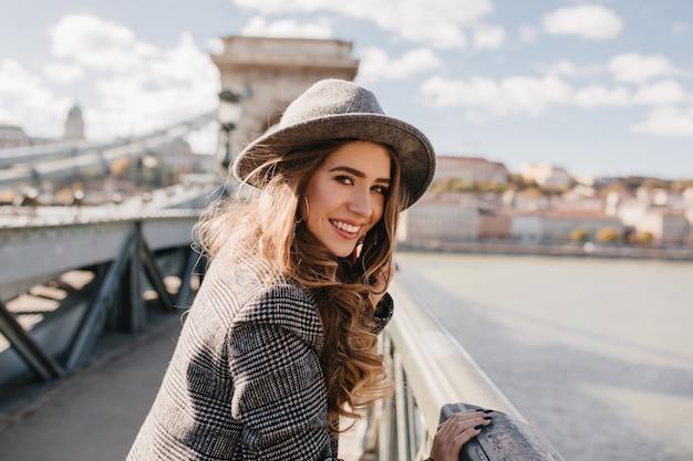 ぼやけた街の背景にbrigeでポーズをとる長い薄茶色の髪の愛らしい女性