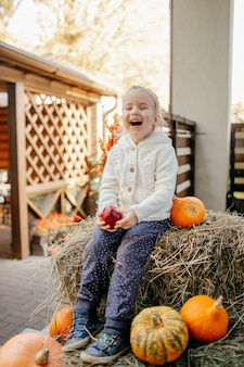 Adorable laughing caucasian baby toddler in white knittes jacket sitting on the haystack with pumpkins at porch and playing with apple.