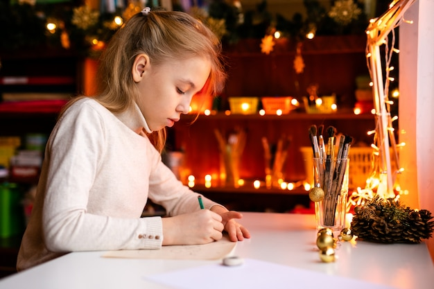 Adorable litle girl is writting a letter to santa klaus sitting on the table