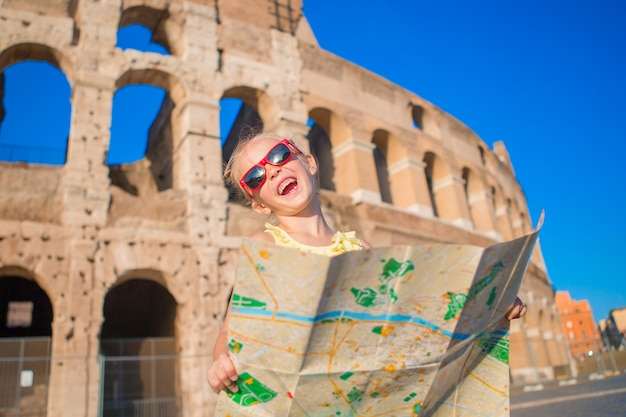 Adorable little active girl with map in front of colosseum in rome, italy.