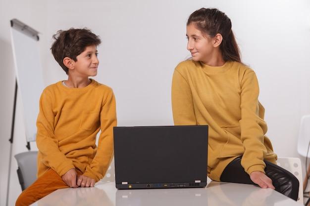 Очаровательный арабский мальчик и его сестра-подросток улыбаются друг другу