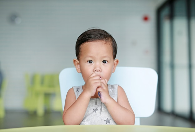 Adorable little asian baby boy eating chocolate in the classroom.
