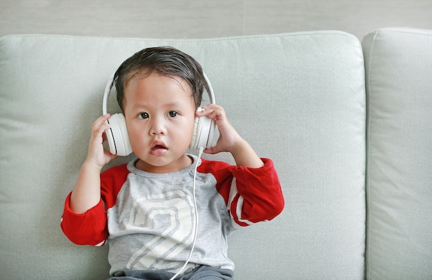 Adorable little asian baby boy in headphones is using a smartphone lying on the sofa at home. child listening to music on earphones.