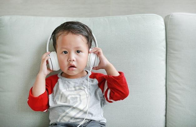 ヘッドフォンで愛らしい小さなアジアの男の子は、自宅のソファに横たわっているスマートフォンを使用しています。イヤホンで音楽を聴いている子供。