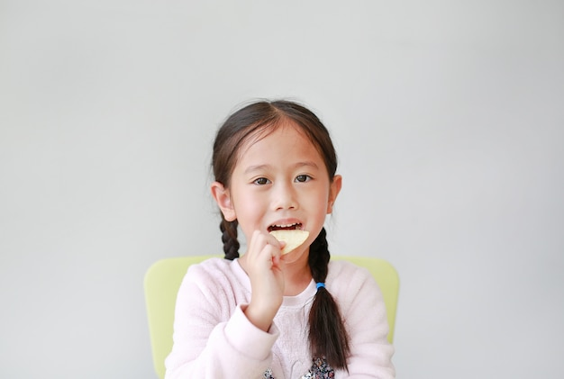 Adorable little asian child girl eating crispy potato chips on white.