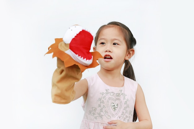 Adorable little asian child girl hand wear and playing lion puppets on white background