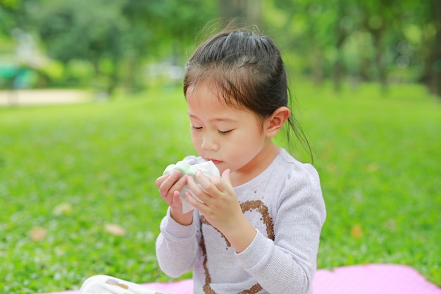 Adorable little asian child girl open the dessert bag and smelling food in her hands at green grass garden.