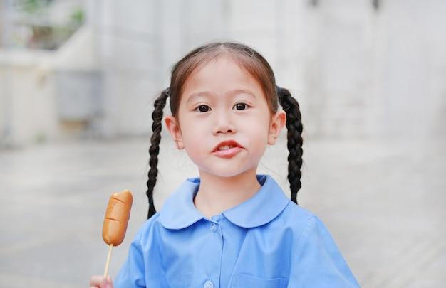 Adorable little asian child girl in school uniform enjoy eating sausage.