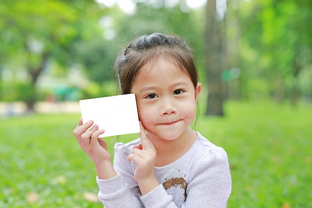 Adorable little asian child girl showing up a blank white paper in the green garden.