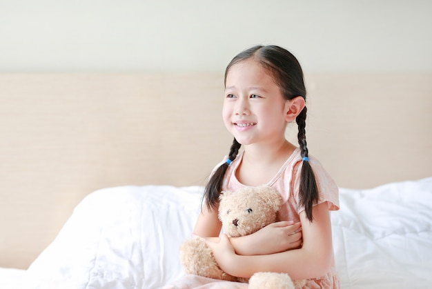 Adorable little asian girl embracing teddy bear while sitting on the bed at home.