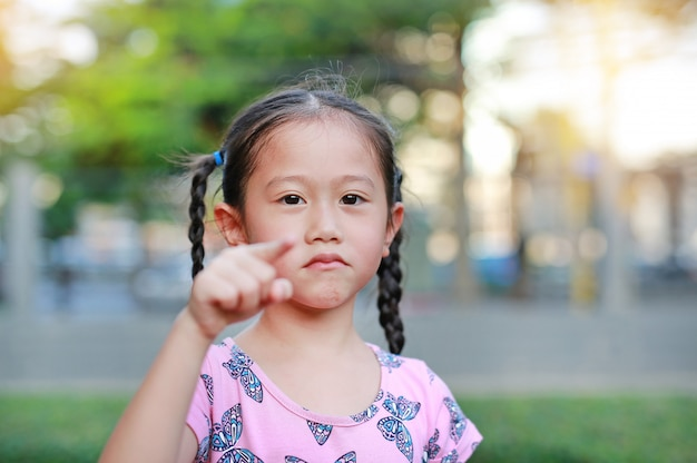 Adorable little asian girl in garden with pointing at camera. portrait smiling kid in park. focus at child face.