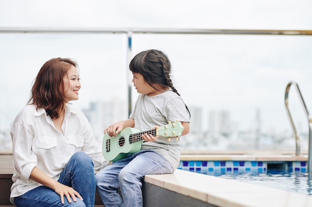 Adorable little asian girl playing ukulele for her happy proud mother