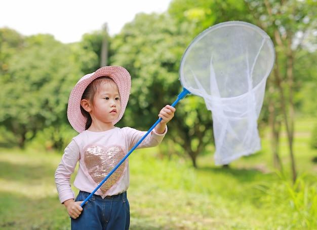 愛らしい小さなアジアの女の子は、夏の昆虫ネットとフィールドの麦わら帽子を着用
