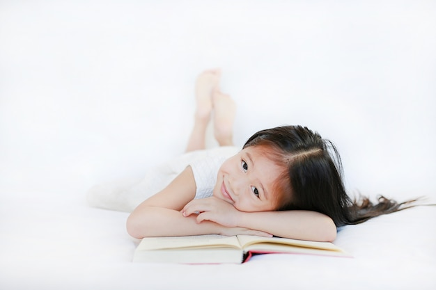 Adorable little asian girl with hardcover book lying on bed and looking camera over white background.