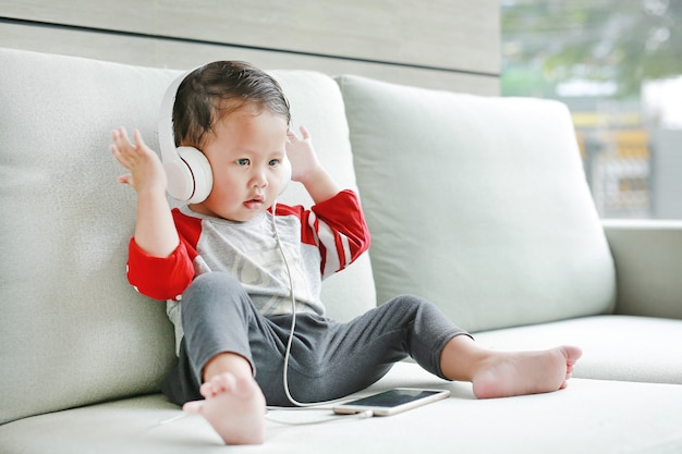 Adorable little baby boy sitting on sofa and listening music at headphones by smartphone
