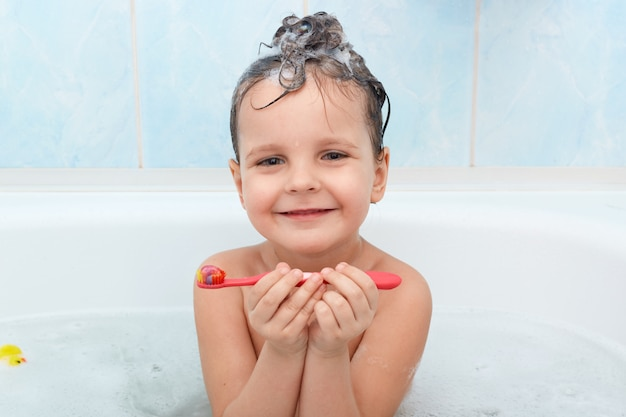 Adorable little baby girl brushing her teeth, taking bath alone, cute little kid glad to wash