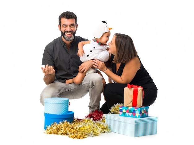 Adorable little baby with his parents at christmas parties on isolated white background