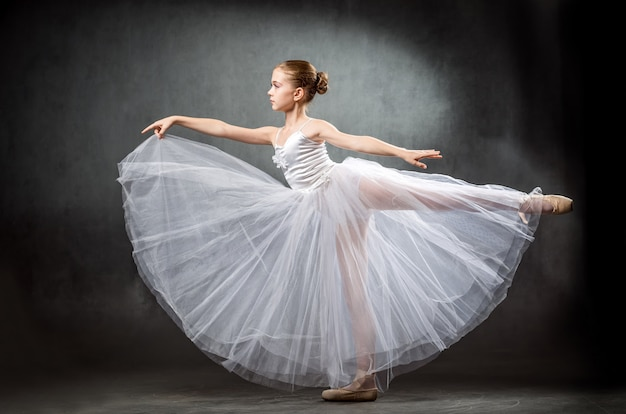 Очаровательны маленькая балерина танцует в студии. девушка изучает балет.