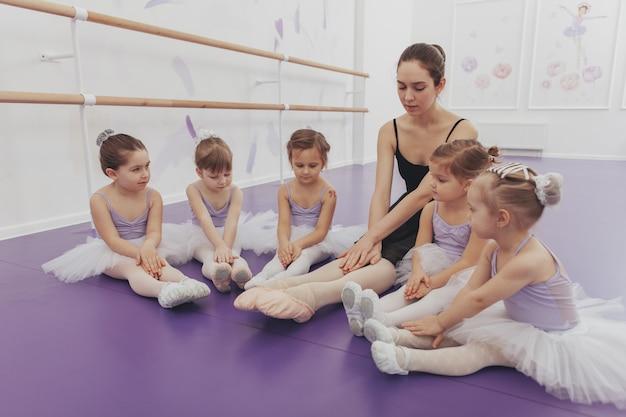 Очаровательные маленькие балерины в купальниках и балетных пачках в балетной школе со своим учителем