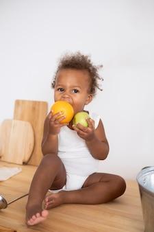 과일을 들고 있는 사랑스러운 작은 흑인 아기