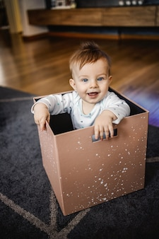 ボックスに座って、笑って、遊んでいる青い目をした愛らしい金髪少年。ホームインテリア。