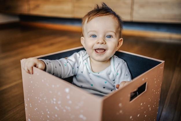 ボックスに座って、笑って、遊んで青い目を持つ愛らしい小さな金髪の少年