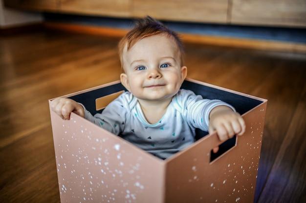 ボックスに座って、笑顔で遊んで青い目をした愛らしい金髪少年