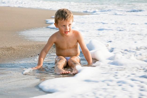 ビーチで楽しんでいる愛らしい小さな金髪の子供の男の子。
