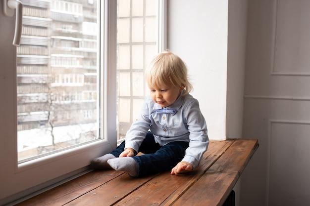 窓辺に座っている愛らしい小さな金髪の子供の男の子。コロナウイルスのテーマ。家にいる。