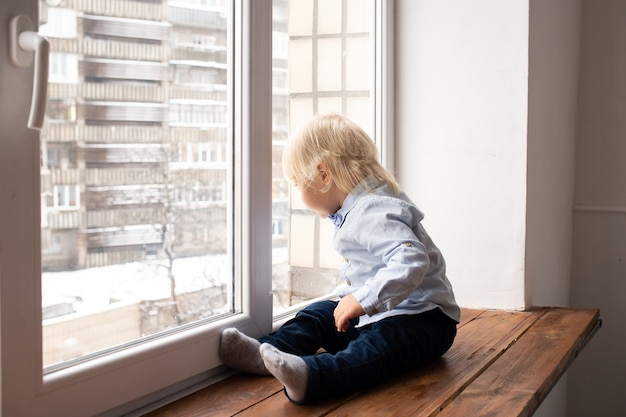 Adorable little blond kid boy sitting on the windowsill. a child looks out the window.