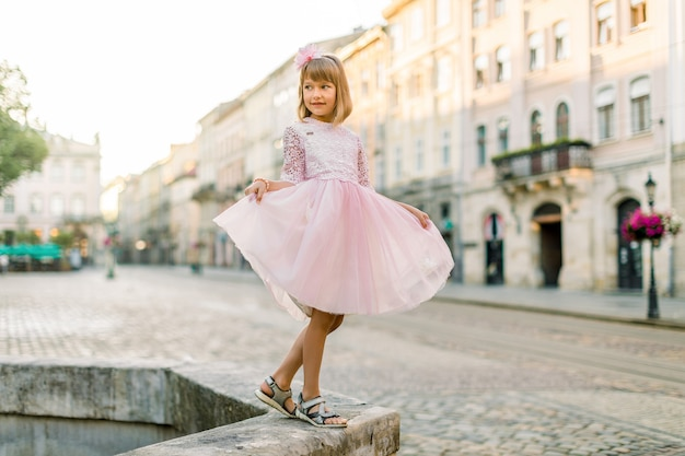 市内のピンクのドレスで愛らしい小さなブロンドの女の子