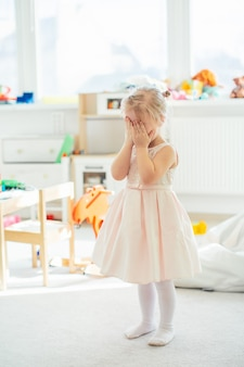Adorable little blonde girl in a pink dress hiding her face behind her hands.